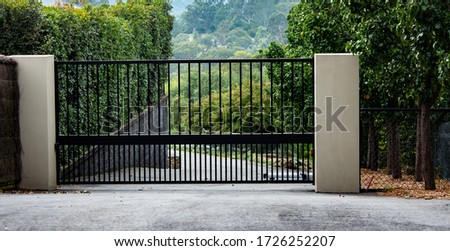 Black metal garden entrance gates set in brick fence with tree covered in orange flowers Royalty-Free Stock Photo #1726252207