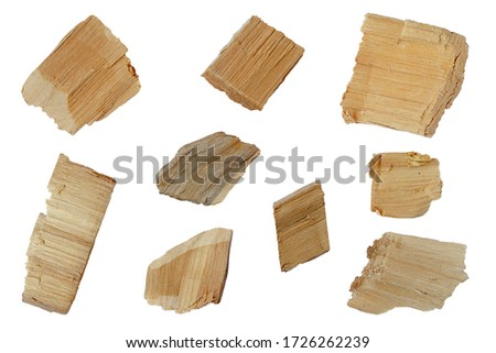 Set of wood chips on a white background. Top view of a group of wood chips on a white background. Oak wood chips. Parts of pine or oak wood chips on a white background, top view. #1726262239