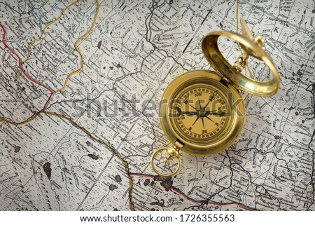 Retro styled golden compass (sundial) and old white nautical chart close-up. Vintage still life. Sailing accessories. Travel and navigation theme Royalty-Free Stock Photo #1726355563