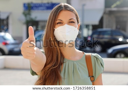 COVID-19 Optimistic young woman wearing protective mask KN95 FFP2 avoiding Coronavirus disease 2019 showing thumbs up in city street #1726358851