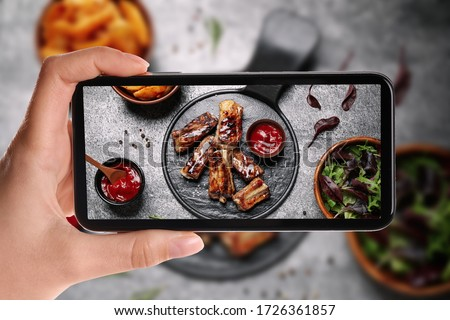 Blogger taking picture of delicious grilled ribs at table, closeup. Food photography