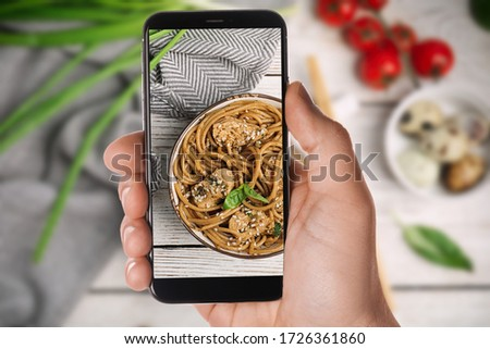 Blogger taking picture of delicious buckwheat noodles with meat at table, closeup. Food photography