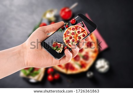 Blogger taking picture of delicious pepperoni pizza at table, closeup. Food photography