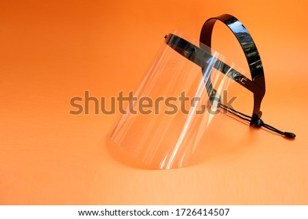 Face protector on an orange background. Face shield used to protect against coronavirus. transparent face protector. Royalty-Free Stock Photo #1726414507