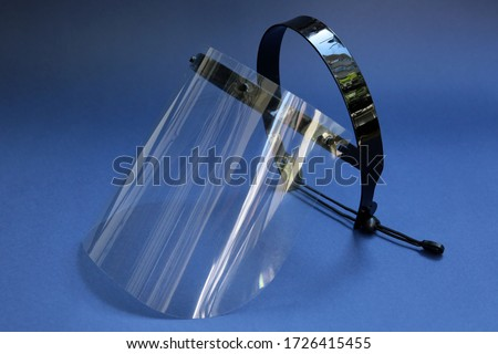 Face protector on a blue background. Face shield used to protect against coronavirus. transparent face protector. Royalty-Free Stock Photo #1726415455