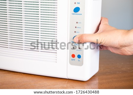 Hand turning on ozone machine generators to cleaning and disinfection during covid 19 epidemic. Details in Spanish. Royalty-Free Stock Photo #1726430488
