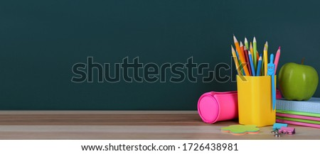 Stationery and apple on table near chalkboard, space for text. Banner design