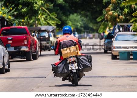 Bangkok, Thailand - May, 05, 2020 : Thailand Post, Postman is delivering packages to customers at Bangkok, Thailand #1726454449