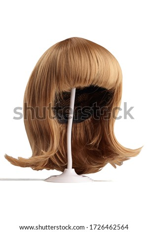 Subject shot of a natural looking blonde wig with bangs and twisted strands fixed on the white wigs holder. The stand with the wig is isolated on a white background.   Royalty-Free Stock Photo #1726462564