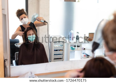 Working during covid-19 or coronavirus concept. A professional hairdresser cutting the hair to a client, reflected in the mirror with copy space. #1726470175