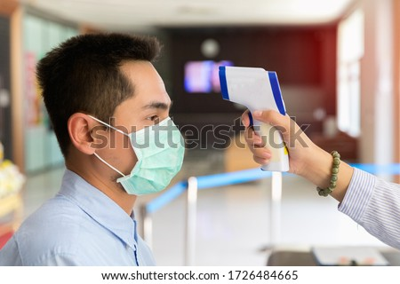 Disease control experts use an Infrared thermometer equipment to check the temperature on the forehead and use alcohol gel to screen the patients addicted to Covid-19 before entering the building. #1726484665
