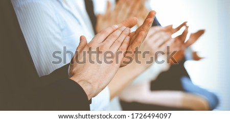 Business people clapping and applause at meeting or conference, close-up of hands. Group of unknown businessmen and women in modern white office. Success teamwork or corporate coaching concept Royalty-Free Stock Photo #1726494097