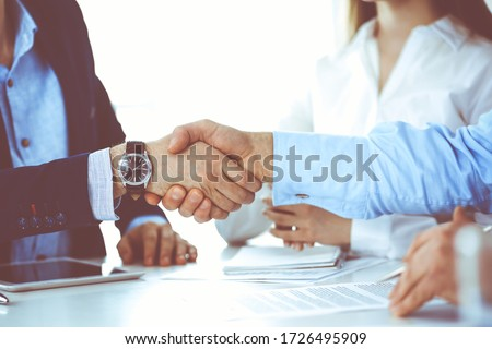 Business people shaking hands at meeting or negotiation, close-up. Group of unknown businessmen and women in modern office. Teamwork, partnership and handshake concept, toned picture #1726495909