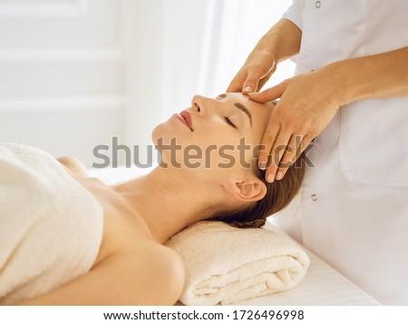 Beautiful woman enjoying facial massage with closed eyes #1726496998