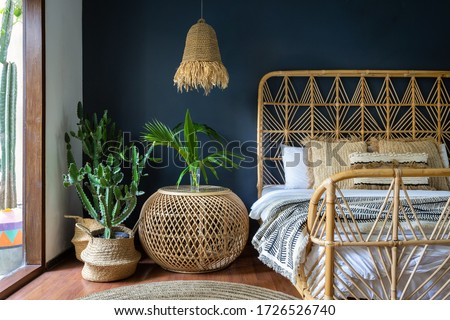 Traditional asian bedroom with ethnic decor, lamp over nightstand table, comfortable bed, carpet or rug, exotical cactus in basket and natural green plant composition. Conceopt of cozy house interior #1726526740