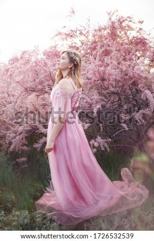 girl in a long dress near blooming tamarix against the setting sun #1726532539