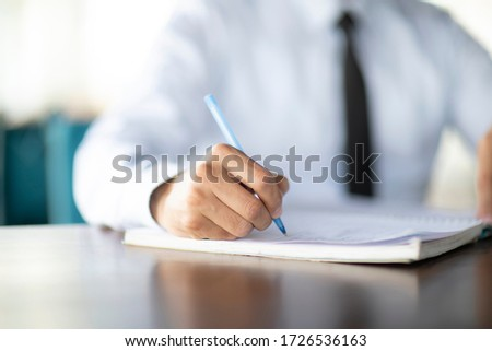 Businessman hand close up writing with pen on the table
