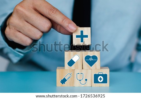 Good Healthcare and Insurance concept.Business hand choose plus sign on wood cube block,Positive quantity,Take care and Safety. #1726536925
