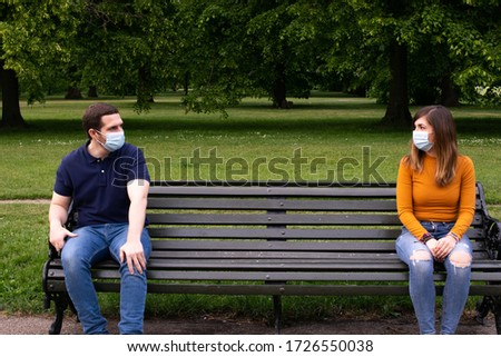 Photo of a young and attractive couple sitting on a bench.  They are wearing a face mask and talking with social distancing in the park