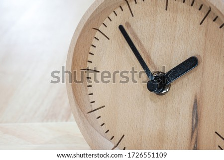 The close-up picture of the wooden table clock with a black dial showing about 2 o'clock on the wooden table as a background with warm light