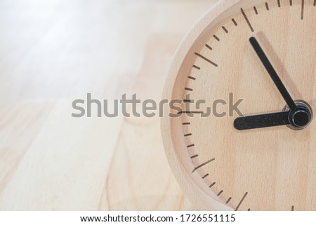 The close-up picture of the wooden table clock with a black dial showing about 9 o'clock on the wooden table as a background with warm light