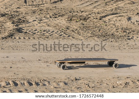 Electric longboard on a dirt covered trail.  Powered skateboard in a dirty construction area, with room for text left and above.  Large ruts and tracks from heavy equipment visible in background. #1726572448