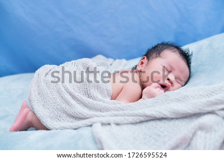 Newborn baby boy lying on his back relaxing under a gray color wrap cloth.with selective focus.Healthy and medical concept. #1726595524
