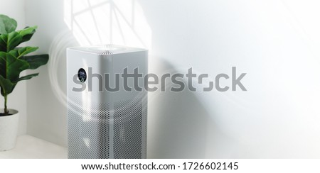 air purifier a living room,  air cleaner removing fine dust in house. protect PM 2.5 dust and air pollution concept Royalty-Free Stock Photo #1726602145