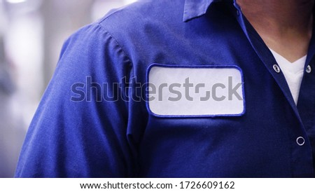 unrecognizable man wearing blue uniform shirt with empty name white tag or patch, worker or employee Identification. Royalty-Free Stock Photo #1726609162