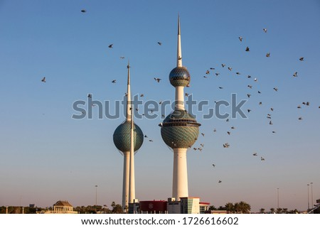 Kuwait City, Kuwait - February 20th 2019 - The iconic Kuwait Towers, which consist of three towers, are set against a blue sky with a flock of birds flying across the foreground.  #1726616602