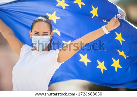Woman in a face mask holding an European union flag behind her back with arms up. Royalty-Free Stock Photo #1726688050