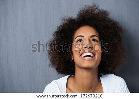Laughing African American woman with an afro hairstyle and good sense of humor smiling as she tilts her head back to look into the air Royalty-Free Stock Photo #172673210
