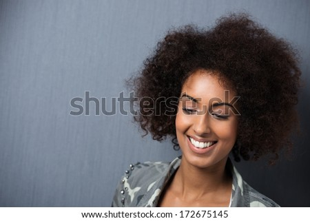 Smiling young African American woman with downcast eyes and a wild afro hairstyle against a dark grey background with copyspace #172675145