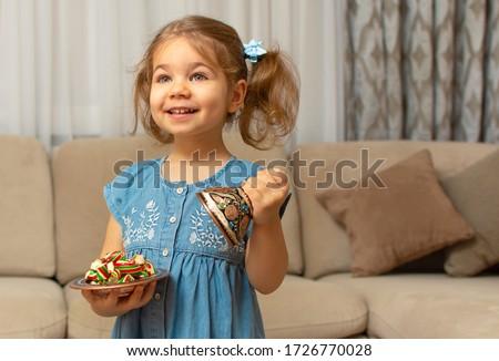 Child and traditional Ramadan candies.  Colorful sweet and baby girl.  Eid Mubarak. Kid hold plate full of sugar during Ramadan kareem (Turkish: Ramazan Bayrami). #1726770028