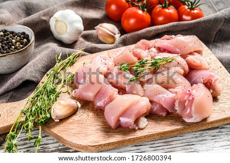 Raw chicken meat fillet cut into cubes on cutting board. White background. Top view #1726800394