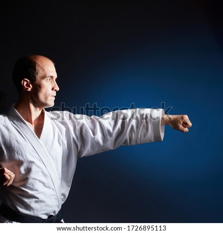 On a blue background in karategi, a young athlete performs a punch arm Royalty-Free Stock Photo #1726895113