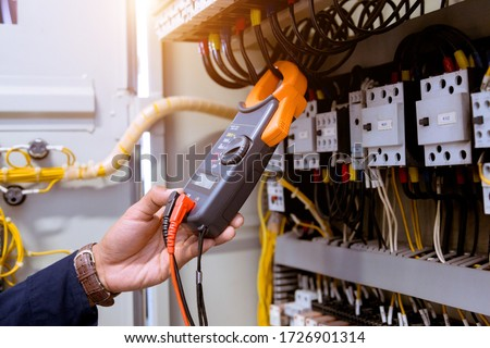 Electrician measurements with multimeter testing current electric in control panel. #1726901314