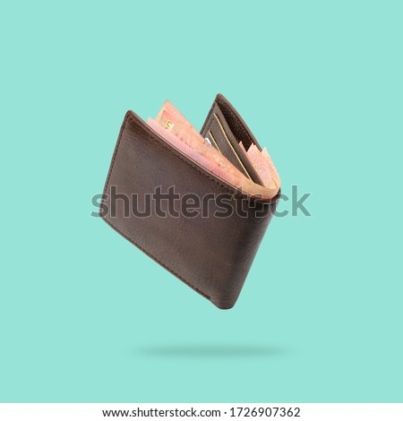 Flying in air Brown genuine leather wallet with banknotes and credit card inside isolated on turquoise background. Royalty-Free Stock Photo #1726907362