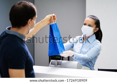 Cashier In Retail Shop Or Store At Counter Wearing Face Mask Royalty-Free Stock Photo #1726918909