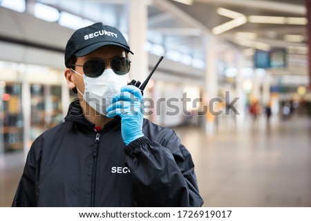 Security Guard Standing In Face Mask In Airport Terminal #1726919017