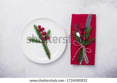 Christmas table setting. White plate and silverware on stone background. Top view. Copy space - Image