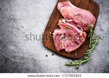 Raw pork meat on wooden cutting board at kitchen table for cooking pork steak roasted or grilled with ingredients herb and spices , Fresh pork #1727005822
