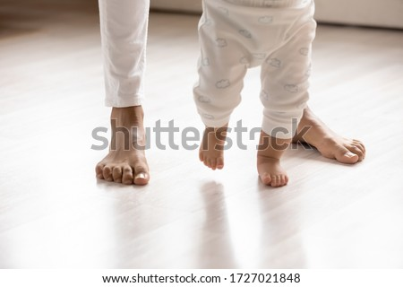 Crop close up of small biracial toddler infant make first steps on home wooden floor holding mom hands, little african American baby child learn walking with mother support care, childcare concept #1727021848
