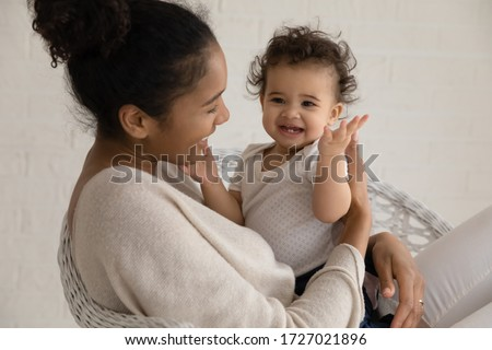 Loving young african American mother hold embrace cute little ethnic infant toddler, caring biracial mom play have fun hug small baby child, enjoy family time at home together, childcare concept #1727021896