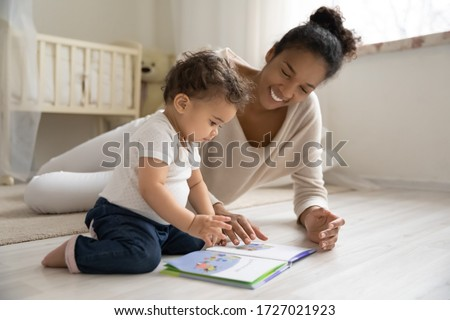 Smiling young african American mother sit on warm floor play with little infant toddler child, happy biracial mom relax have fun read book with small baby girl at home, motherhood, childcare concept Royalty-Free Stock Photo #1727021923