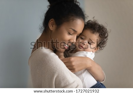 Close up of loving biracial young mom hug cuddle little ethnic infant toddler, happy caring african American mother embrace lull small baby girl child, enjoy tender moment, childcare concept #1727021932