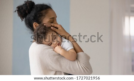 Caring young biracial mother hold lean to chest cute little infant toddler, loving african American mom hug embrace small baby child, relax enjoy tender family moment at home, childcare concept #1727021956