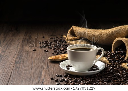 Hot coffee in a white coffee cup and many coffee beans placed around and sugar on a wooden table in a warm, light atmosphere, on dark background, with copy space. #1727031229