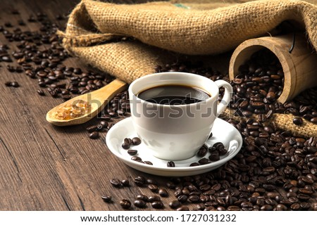 Hot coffee in a white coffee cup and many coffee beans placed around and sugar on a wooden table in a warm, light atmosphere, on dark background, with copy space. #1727031232