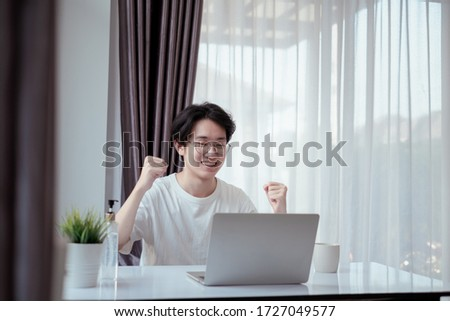 Asian man success wokring from home office happy and smiling on laptop computer, studying e-learning smart online when quarantine crisis coronavirus, covid-19 prevention reduce risk new normal. #1727049577